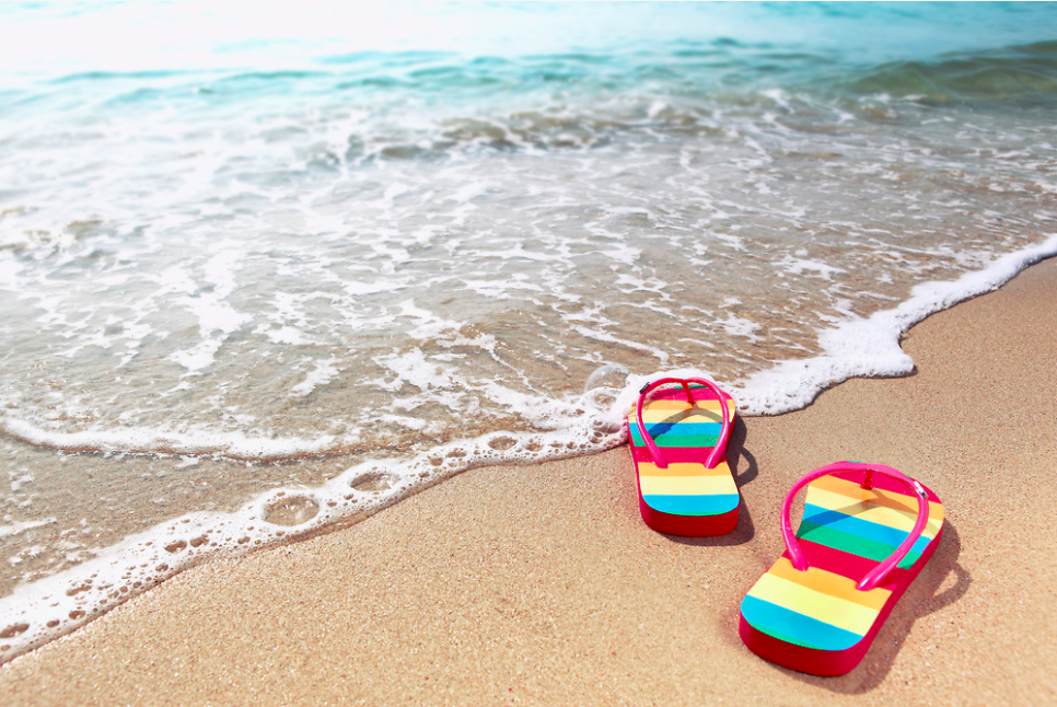 The image shows a single colorful pair of flip flops on a quiet beach to illustrate the idea that Northern Trail Outfitters and other retail marketers are considering that fewer consumers are taking tropical vacations during the pandemic.